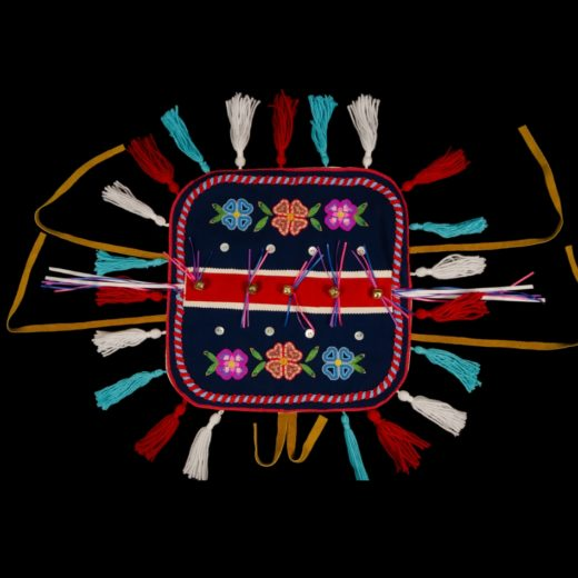 Yukon Permanent Art Collection 2017, Tourism and Culture, Arts Branch Artist: Nyla Klugie-Migwans Title: Traditionhal First Nations Dog Blanket Project Year: 2017 Materials: Melton, canvas backing, satin ribbon, ric-rac ribbon, mother of pearl buttons, wool and cotton yarn, silver bells, seed beads