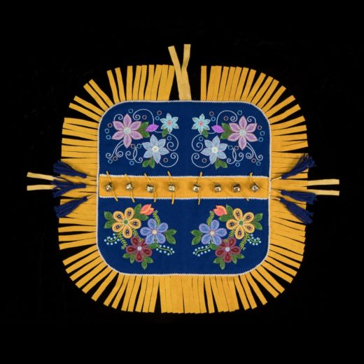 Yukon Permanent Art Collection 2017, Tourism and Culture, Arts Branch Artist: Pauline Livingstone Title: Traditional First Nations Dog Blanket Project Year: 2017 Materials: Melton, canvas backing, commercial moose hide, wool yard, gold-tone, bells and gold-tone cones, seed beads